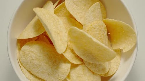 Potato crisps falling into a white bowl