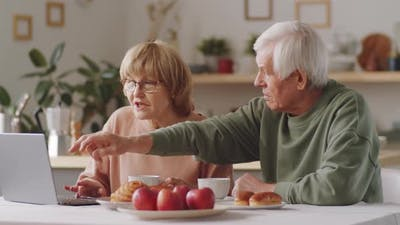 Senior Couple Discussing News on Laptop at Breakfast