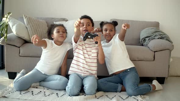 Happy African American Kids Playing Video Game with Joystick at Home