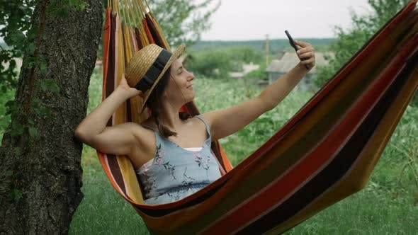 Young happy woman taking selfie photo with mobile phone lying on hammock
