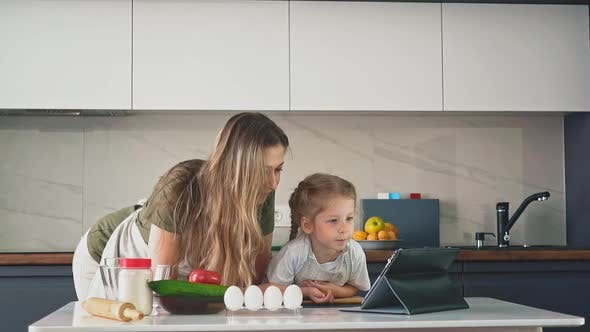 Cover Image for Girl and Mother Watch Food Video Blog at Table in Kitchen