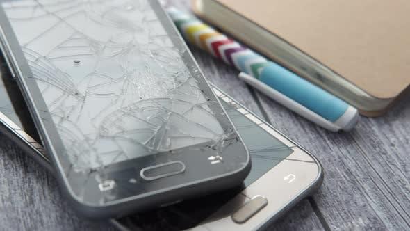 Close Up of Broken Smart Phone on Wooden Background