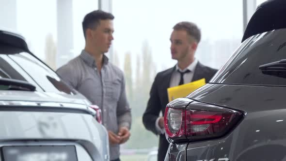 Thumbnail for Selective Focus on a Car, Male Customer Talking To Auto Dealer on the Background