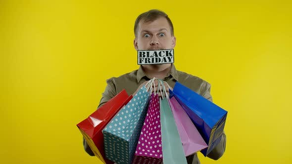Surprised Man Showing Shopping Bags and Black Friday Inscription in His Mouth, Yellow Background