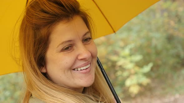 Caucasian blond woman outdoor with yellow umbrella 4K 2160p 30fps UltraHD footage - While raining bl