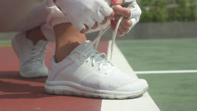 Manicured Nails Tying Shoelaces of White Tennis Shoes