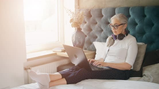 Thumbnail for Elderly Woman Typing on Laptop in Bedroom