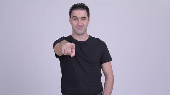 Thumbnail for Happy Handsome Man Pointing at Camera Against White Background
