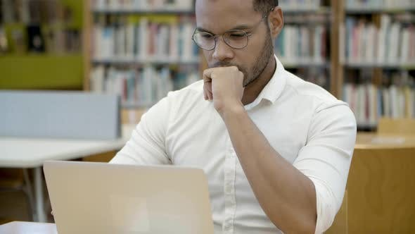 Thumbnail for Focused Young Man Working with Laptop in Library