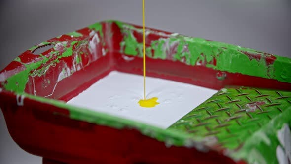 Thumbnail for A Person Pouring Yellow Paint in the Paint Tray with White Paint