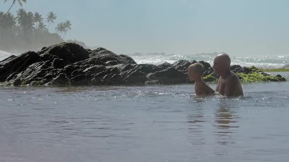 Thumbnail for Daddy Helps Son Jump in Calm Sea Water at Exotic Resort