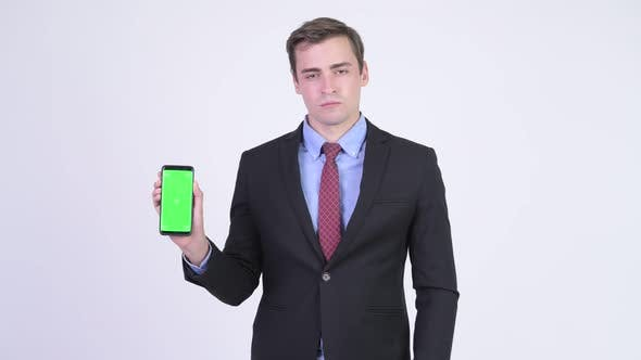 Cover Image for Young Happy Handsome Businessman Showing Phone and Giving Thumbs Up