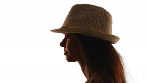Silhouette of young woman in fedora on white background
