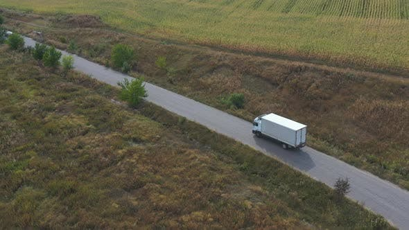 Thumbnail for Aerial Shot of Truck with Cargo Trailer Driving on Road and Transporting Goods. Flying Over Delivery