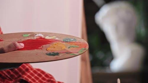 Une jeune femme dans l'atelier d'art Mettre une couleur orange et bleue sur la palette et la mélanger