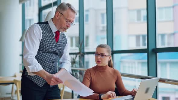 Mature businessman shows papers his secretary