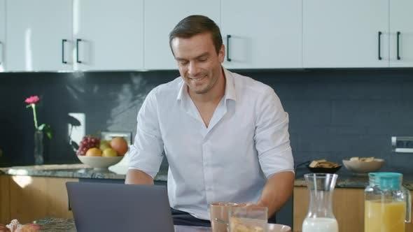 Thumbnail for Smiling Man Talking at Laptop in Luxury Kitchen. Closeup Man Having Online Chat
