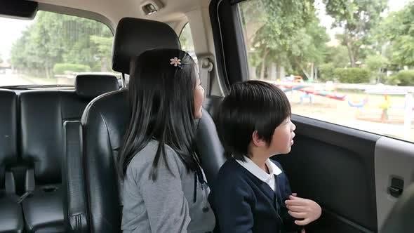 Glückliche asiatische Kinder Reisen mit dem Auto