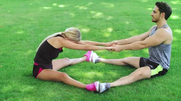 Thumbnail for Fitness Trainer Help Woman Stretching Legs at Warm Up Training in Park