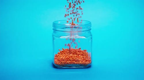 Closeup of Falling Down Red Lentils Into Glass Jar on Blue Background