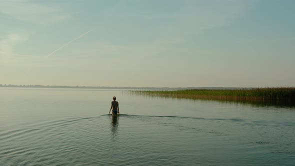 Thumbnail for Aerial Drone View, Attractive Young Woman Walking in a Lake at Summer Day. V2