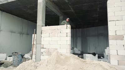Construction Worker Builds a White Brick Wall