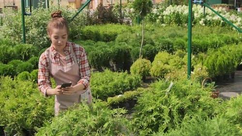 Female Gardener Using Smartphone In Yard
