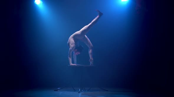 Thumbnail for Acrobat Girl on Stage Does Acrobatic Stunts Standing on Her Hands