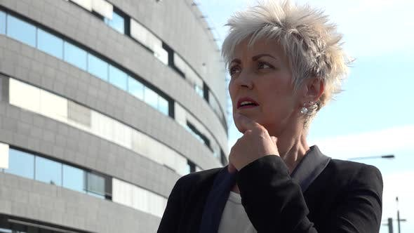 Thumbnail for A Middle-aged Woman Looks Thoughtfully Around a Street in an Urban Area - an Office Building
