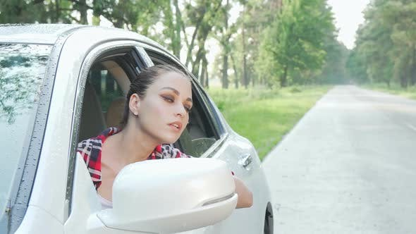 Young Woman Sitting in Her Car Looking Around on Countryside Road