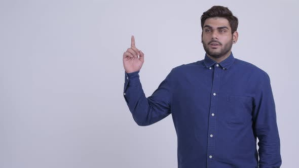 Thumbnail for Happy Young Bearded Indian Businessman Thinking and Pointing Up
