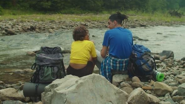 Romantic Loving Multicultural Couple Hikers Embracing Near Beautiful Mountain River on Trek