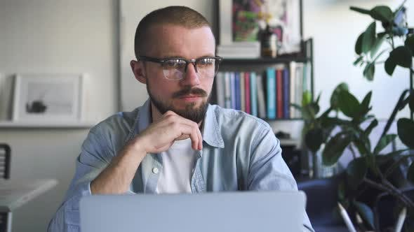 Thumbnail for Front View of Young Bearded Businessman Working with Laptop at Table in Home. Spbd