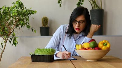 Nutritionist, dietitian woman speaking and writing a diet plan,