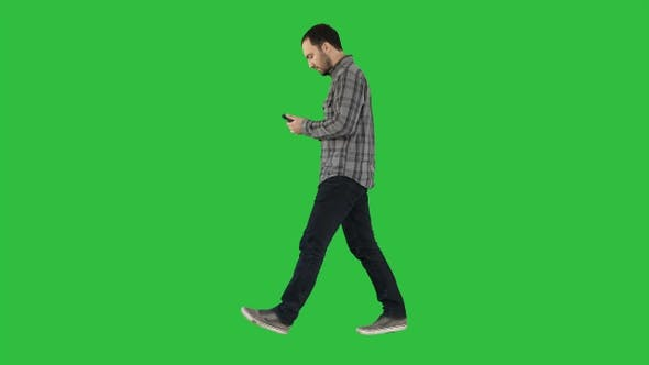 Thumbnail for Young smart casual man walking and reading message on cell