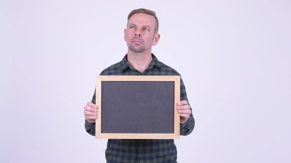 Thumbnail for Portrait of Happy Blonde Hipster Man Thinking While Holding Blackboard