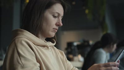 Woman With Smartphone In Cafe