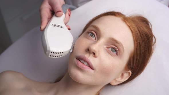 Cosmetologist Performs Laser Treatment of the Skin of the Face in Order To Rejuvenate Women's Skin