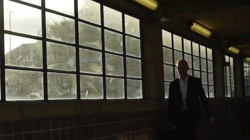 Businessman in suit walking through covered passageway on commute to work, static shot