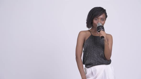 Thumbnail for Happy Young Beautiful African Woman Presenting Something with Microphone