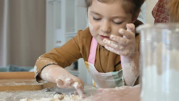 Mom and Daughter Prepare Holiday Cookies Together in the Kitchen. A Little Girl Helps Her Mother