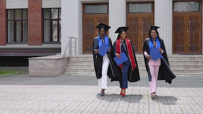 Happy Graduates of a University or College of African American Nationality with Blue Diplomas in
