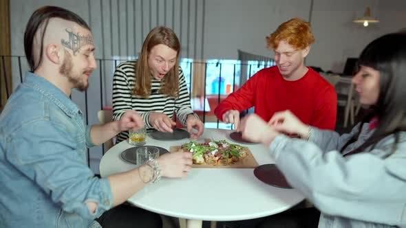 Vier junge kaukasische Männer und Frauen teilen sich Pizza am Tisch im Restaurant