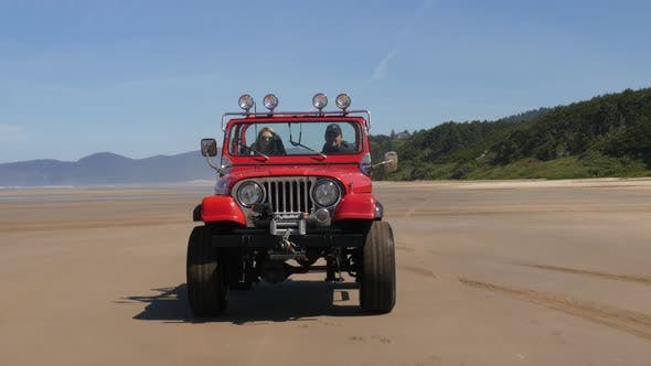 Couple driving 4x4 off road vehicle driving on beach