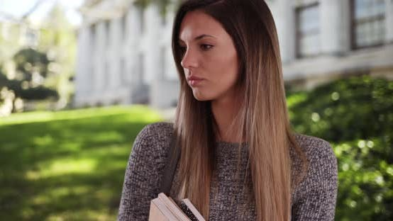 Thumbnail for Young Caucasian female college student looking somber on college campus outside