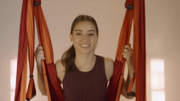 Woman Swinging in Hammock at Yoga Studio. Girl Sitting in Hammock for Aero Yoga