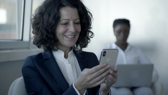 Thumbnail for Cheerful Businesswoman Using Smartphone