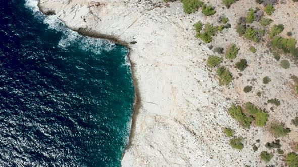 Cover Image for Drone Flying Along Rocky Coast Line and Dreep Blue Sea Water