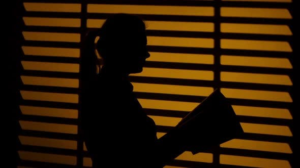 Thumbnail for Girl Leafing Through a Book. Book in the Hands. Silhouette. Close Up