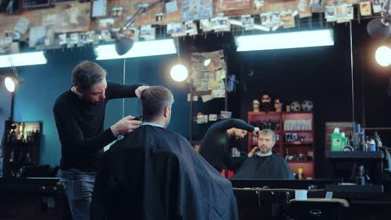 Man Makes a Haircut in a Brutal Stylish Hairdresser. Client Sits in a Chair in Front of the Mirror